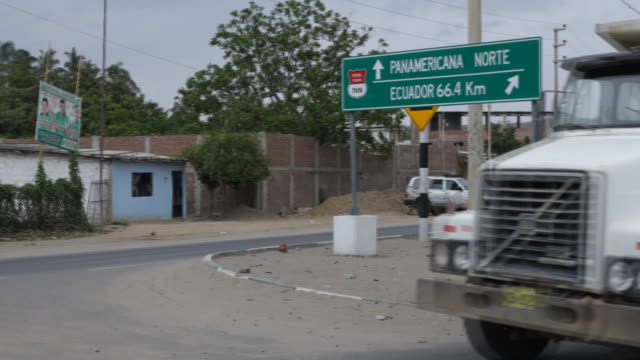 sign at a road's intersection shows the way to the panamerican highway and to ecuador traffic is passing by the panamerican highway links almost all... - pan american highway stock videos & royalty-free footage