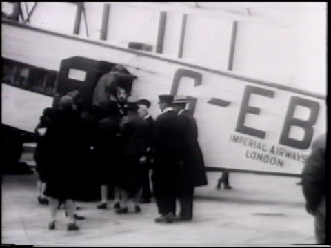 sign at airfield 'arriving/departing for from paris, rotterdam, amsterdam, cologne', passengers boarding imperial airways london c-ebix bi-plane,... - passenger stock videos & royalty-free footage