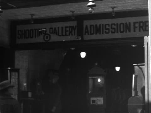 b/w 1906 sign at entrance to shooting gallery / new york city / newsreel - 1906 stock-videos und b-roll-filmmaterial
