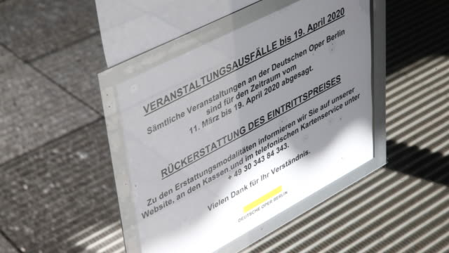 a sign at the entrance of the opera deutsche oper berlin informs visitors that the opera is closed following a city ordinance temporarily closing all... - geschäftliche aktivitäten stock-videos und b-roll-filmmaterial