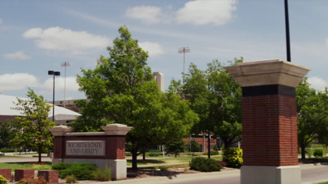 sign at wichita state university with football stadium in background - wichita stock-videos und b-roll-filmmaterial