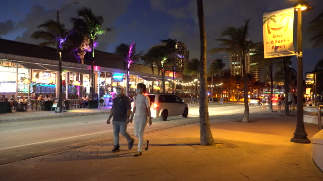 a sign attached to a light post on fort lauderdale beach boulevard reminds people to stay 6 feet apart as pedestrians some wearing face coverings... - scott mcpartland stock videos & royalty-free footage