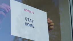 STAY HOME sign being applied to window.