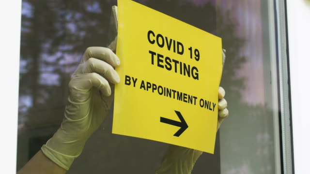 covid-19 testing sign being placed in window. - hospital stock videos & royalty-free footage