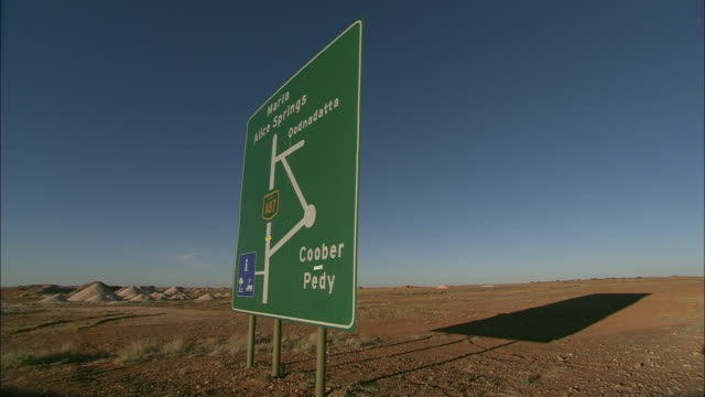 a sign casts a shadow on a barren plain at coober pedy, australia. - coober pedy stock videos & royalty-free footage