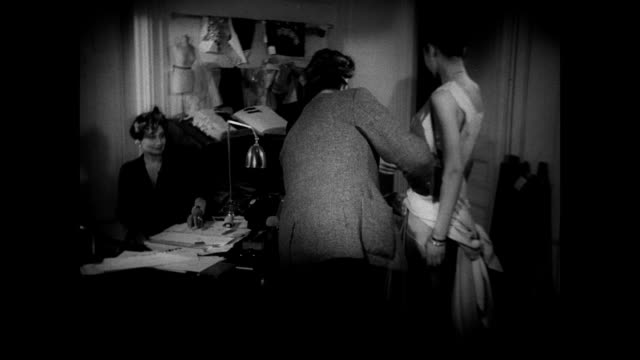 Sign 'Christian Dior' INT MS Designer Dior w/ female assistant dressing French model in sleeveless evening gown Paris