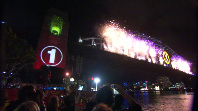A sign counts down as fireworks explode during a New Year's celebration in Sydney, Australia.