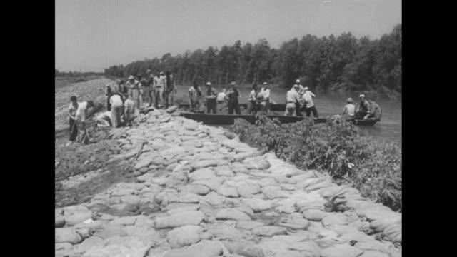 "sign ""danger levee construction"" above speed limit sign / men stacking sandbags at shoreline / sandbag workers taking a break to eat / women handing... - river mississippi stock videos & royalty-free footage"