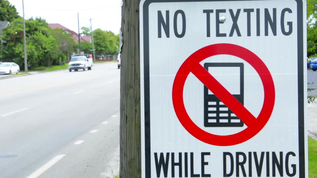 no texting while driving sign dangerous practice - verboten stock-videos und b-roll-filmmaterial