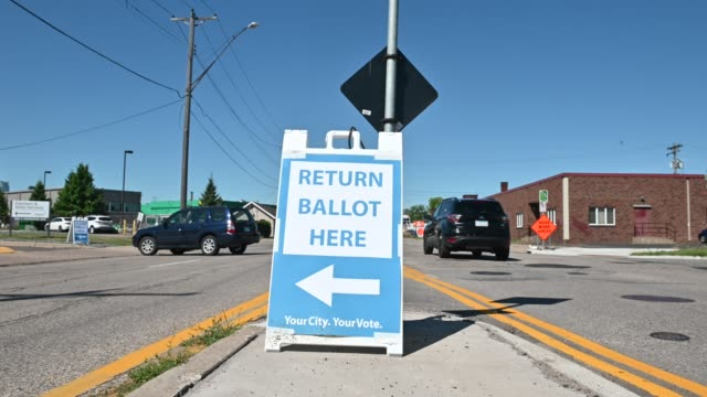 sign directs where to return ballots as drivers arrive at a drive through drop-off for absentee ballots for the minnesota state primary elections on... - ballot slip stock videos & royalty-free footage