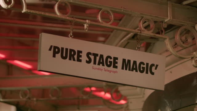 """sign displaying a newspaper critic's review reading """"'pure stage magic' sunday telegraph"""" hangs from a west end theatre, london, uk. - critic stock videos & royalty-free footage"""