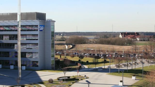 a sign displays the sap ag logo outside the businesssoftware maker's headquarters in walldorf germany on monday feb 24 the sap ag headquarters stand... - hauptfirmensitz stock-videos und b-roll-filmmaterial