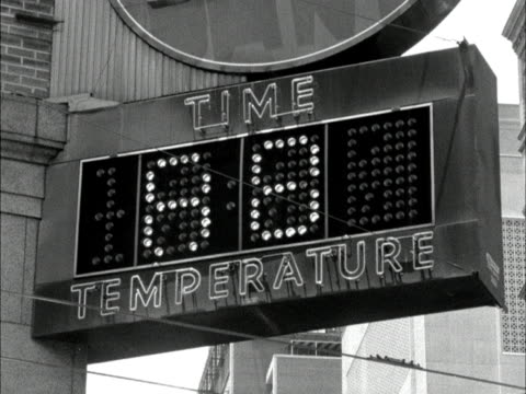 a sign displays the time and temperature in atlanta 1961 - bankenschild stock-videos und b-roll-filmmaterial
