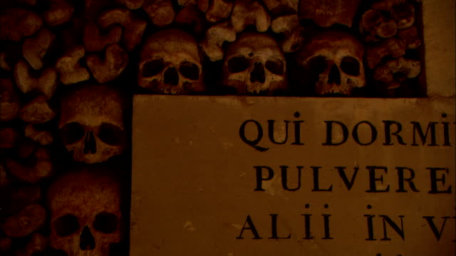 a sign displays the words from daniel, chapter 12, verse 2 in latin over a wall of human bones in the catacombs of paris. - christianity stock videos & royalty-free footage