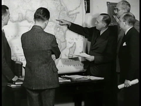 stockvideo's en b-roll-footage met sign 'division near eastern affairs' ms men looking at africa map in office cu two men talking ext car pulling up to us consulate building int george... - 1938