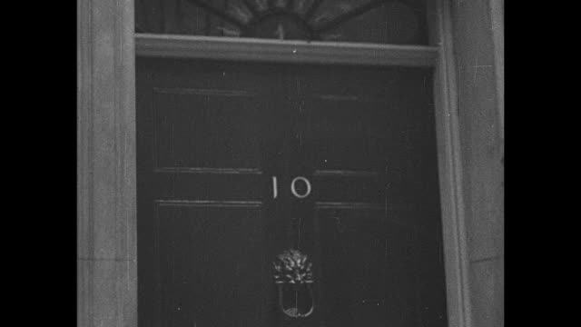 downing st / pan down 10 on door to lion doorknocker / prime minister neville chamberlain stands at entry gates to the residence / sir anthony eden... - door knocker stock videos & royalty-free footage