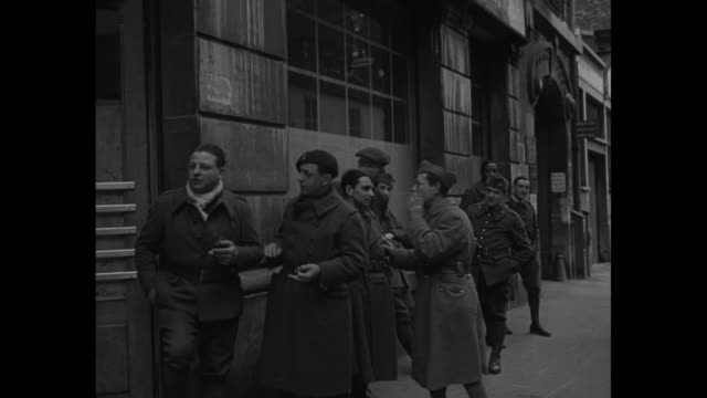sign ecole pratique de coiffure on side of building tilt down to line of soldiers on sidewalk / seated men with one following woman in white uniform... - 1940 stock videos & royalty-free footage
