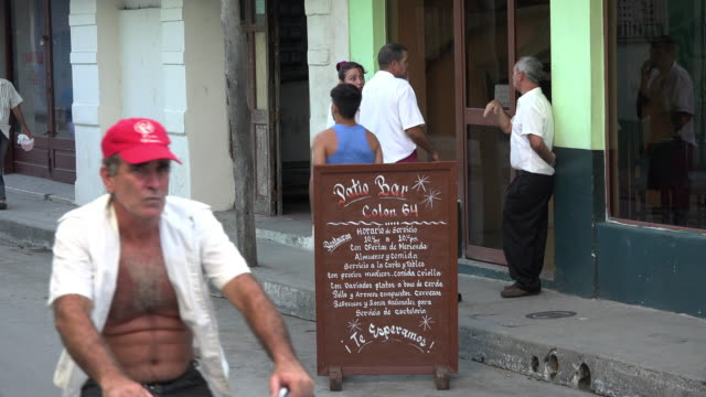 vídeos de stock e filmes b-roll de sign for a restaurant in colon street, santa clara, cuba. workers wearing white shirts in the sidewalk talk to each others because at this point the... - cultura latino americana