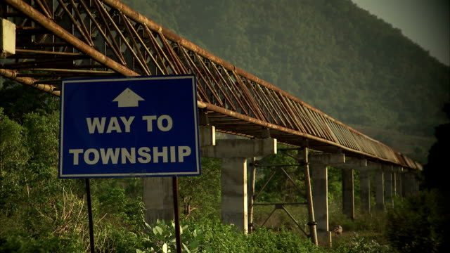 a sign for a township outside the vedanta bauxite mine and refinery in orissa, india. available in hd - indian arrowhead stock videos and b-roll footage
