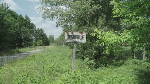 stockvideo's en b-roll-footage met sign for abandoned village of zymovyshche, ukraine, near chernobyl, on june 17, 2019. the chernobyl disaster was a catastrophic nuclear accident that... - kernramp van tsjernobyl
