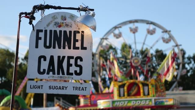 vídeos y material grabado en eventos de stock de sign for fairground food with carnival rides in the background at the delaware county fair. - utensilio para cocinar