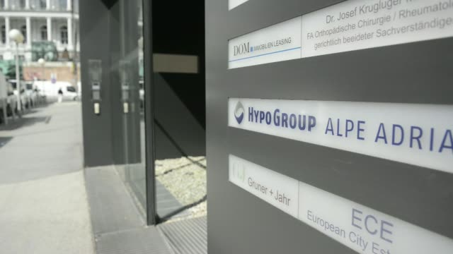 a sign for hypo group alpe adria bank hgaa sits at entrance to office building in vienna austria on wednesday march 26 visitors exit and enter a... - spire stock videos & royalty-free footage