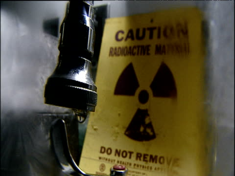 Sign for radioactive material with leaking tube in foreground