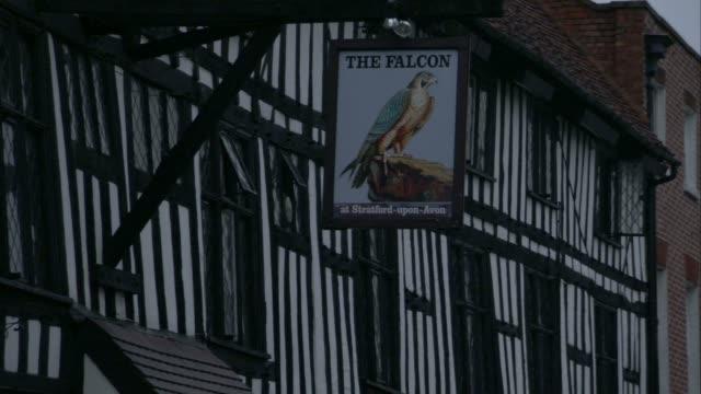 vídeos de stock e filmes b-roll de a sign for 'the falcon' pub hangs outside a tudor building, stratford upon avon. available in hd. - tudor