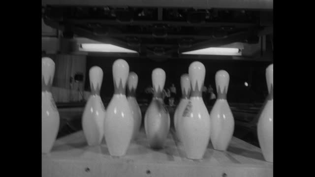 sign golden jubilee over curtains / banner 1953 record entry / vs bowling pins and automatic pin setter / vs low angle view of bowler during game - ボーリング場点の映像素材/bロール