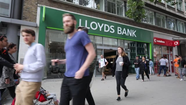 A sign hangs above a Lloyds bank branch a unit of Lloyds Banking Group Plc in London UK on Friday Aug 4 Pedestrians pass a Lloyds bank branch