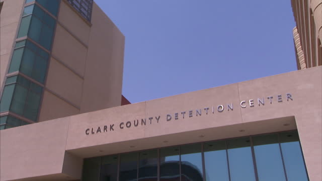 a sign hangs above windows at the clark county detention center in las vegas, nevada. - clark county nevada stock videos & royalty-free footage