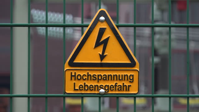 stockvideo's en b-roll-footage met sign high voltage, danger of life, on fence - bord hoogspanning
