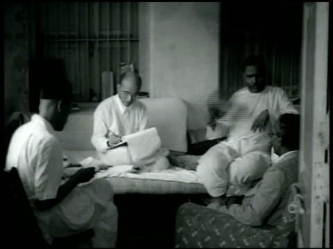 sign hindu mahasabha hindu nationalist vinayak damodar savarkar [aka swantantryaveer savarkar] sitting on bed talking w/ others vs people gathered in... - hinduism stock videos & royalty-free footage