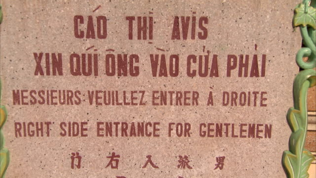 a sign identifies the correct entrance for men into the cao dai temple. - tay ninh stock videos & royalty-free footage