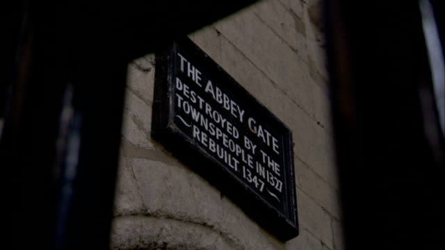 a sign identifies the destruction and rebuilding of abbey gate, bury st edmunds. available in hd. - bury st edmunds stock videos & royalty-free footage