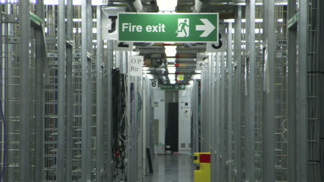 A sign in a computer server room points toward a fire exit.