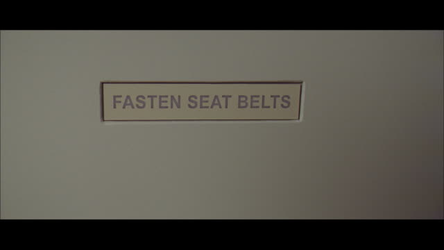 WS Sign in airplane reading FASTEN SEAT BELTS flashing on then off