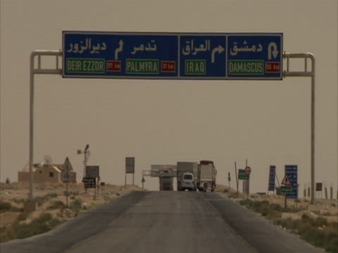 vídeos y material grabado en eventos de stock de sign in desert for palmyra, damascus and baghdad, lorries driving down road, some turn right towards iraq, syria (sound available) - siria