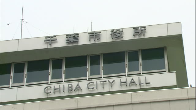 A sign in English and one in Japanese script identify Chiba City Hall in Japan.