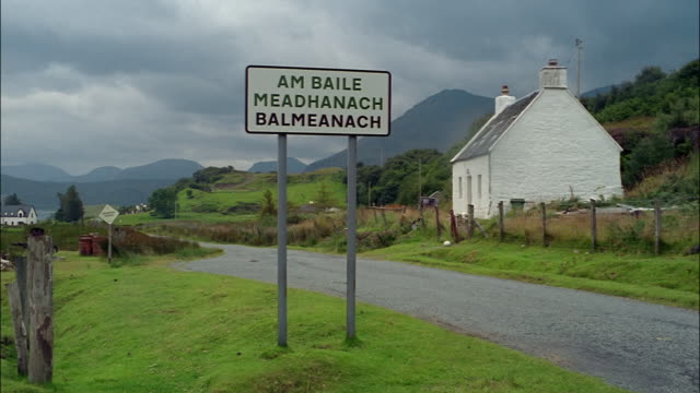 a sign in gaelic identifies a town on the isle of skye in scotland. - insel skye stock-videos und b-roll-filmmaterial