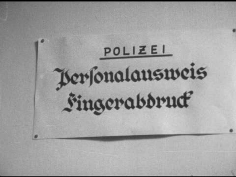 sign in german for 'fingerprinting' vs various east berlin refugees at table filling out personal history forms berlin wall occupied city - rifugiato video stock e b–roll