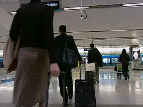 vidéos et rushes de various ws ms mcu la ra dolly in sign in train station, and people walking to train with luggage on moving walkway. - âges mélangés