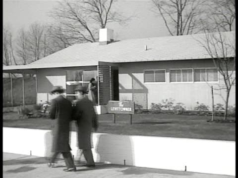 Sign in yard 'Levittowner' VS People walking sidewalk some entering model home
