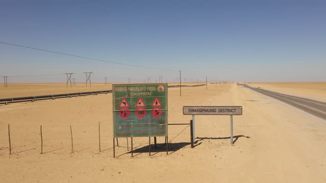 sign indicating the beginning of the swakopmund district and a warning sign of the namib-naukluft park stand along the road in swakopmund, namibia,... - road warning sign stock videos & royalty-free footage