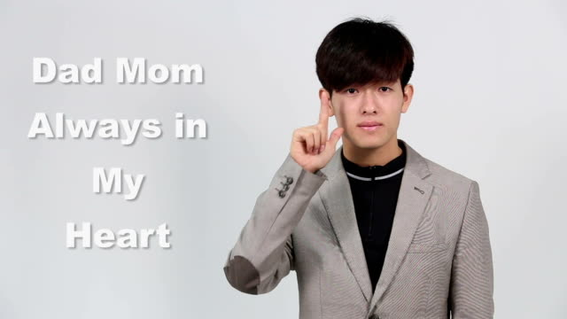 "sign language by asian man in suit jacket over gray background, mean ""dad mom always in my heart"" - suit jacket stock videos & royalty-free footage"