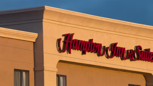 a sign marks a building as hampton inn & suites. - inn stock videos and b-roll footage