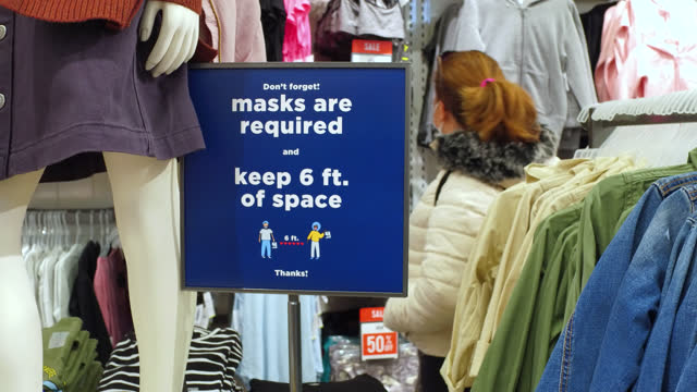 stockvideo's en b-roll-footage met sign of 'mask required' inside of a retail store seen on november 2, 2020; in toronto, ontario, canada. using protective face masks in closed... - plaatselijk monument