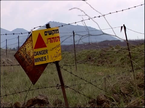 a sign on a barbed wire fence warns of mines in surrounding fields. - land mine stock videos and b-roll footage