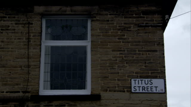a sign on a brick house identifies titus street in saltaire, england. available in hd. - brick house stock videos & royalty-free footage