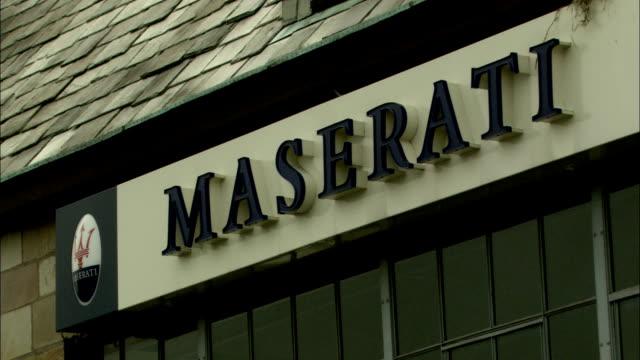 A sign on a building bears the company name 'Maserati.' Available in HD.
